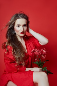 Romantische frau mit langen blonden haaren und blumen in ihren händen in einem roten kleid
