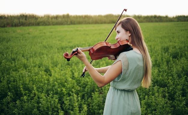 Romantische frau mit losen haaren, die geige spielt. sonnenuntergangslicht in der natur. geigenunterricht