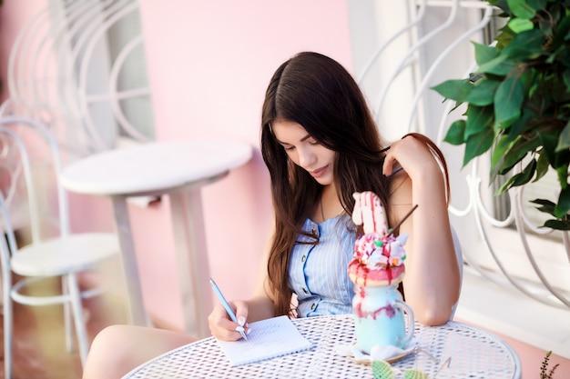 Romantische frau schreibt etwas in ihr notizbuch, während sie im straßencafé sitzt.
