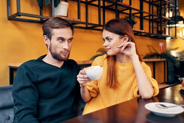 Romantische frau umarmt einen jungen mann in einem pullover an einem tisch in einem café-interieur