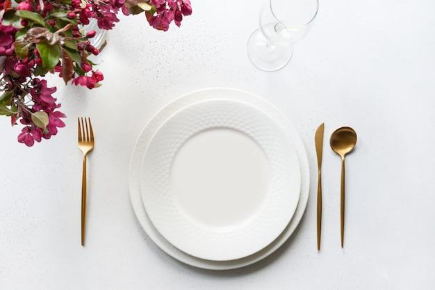 Romantische frühlingstabelleneinstellung mit apfelbaumblumen auf weißem tisch.