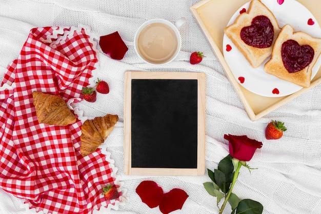 Romantische frühstücksanordnung mit leerem brett