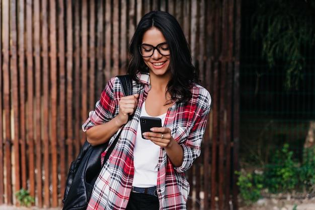 Romantische gebräunte frau, die draußen mit rucksack und smartphone steht. freudiges lateinamerikanisches mädchen in der brille las telefonische nachricht mit lächeln.