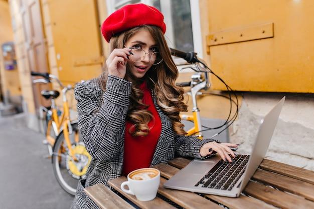 Romantische geschäftsfrau, die mit laptop arbeitet, während kaffee am kalten herbsttag trinkt