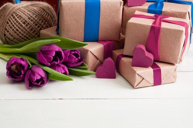 Romantische geschenkboxen mit blumen auf weißer holzwand