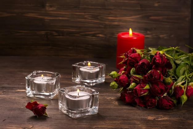 Romantische grußkarte: bündel rosen und kerzen über dunklem hölzernem hintergrund