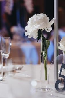 Romantische hochzeitstischdekoration mit großen, üppigen blumensträußen, darunter weiße rosen, ranunkeln, persische butterblumen, weiße orchideen und kerzen