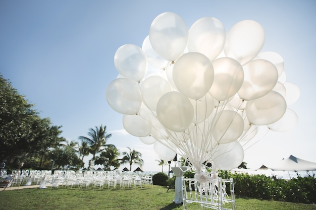 Romantische hochzeitszeremonie am strand. viele weiße luftballons