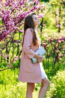 Romantische hübsche junge frau mit langen haaren im rosa mantel