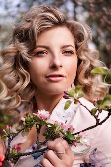 Romantische junge frau im frühlingsgarten unter apfelblüte. schöne frau, glücklicher frühling