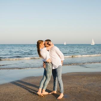 Romantische junge paare, die sommerferien am strand genießen
