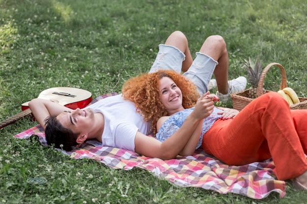 Romantische junge paare, die zusammen im park picknicken