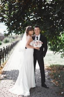 Romantische jungvermählten, braut und bräutigam des glücklichen paars stehen und halten blumenstrauß von rosa und purpurroten blumen und von grüns, grün mit band im garten. hochzeitszeremonie auf natur.