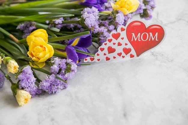 Romantische komposition mit bouquet aus gelben narzissenblüten und lila iris-statice-blüten. glücklicher muttertag mit kopierraum.