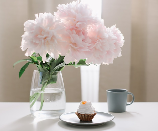 Romantische komposition mit schönen rosa pfingstrosen in einer vase und einer tasse kaffee zu hause