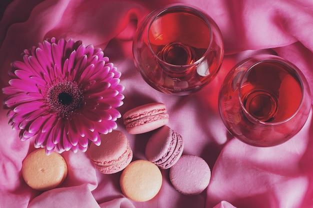 Romantische komposition von blumen, süßigkeiten und wein auf einem rosa hintergrund