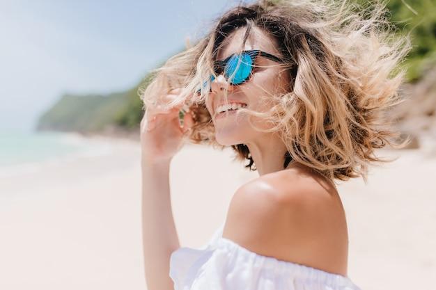 Romantische kurzhaarige frau mit schönem lächeln, das auf verschwommener natur aufwirft. charmante gebräunte frau in der sonnenbrille, die lacht, während sie am exotischen strand ruht.