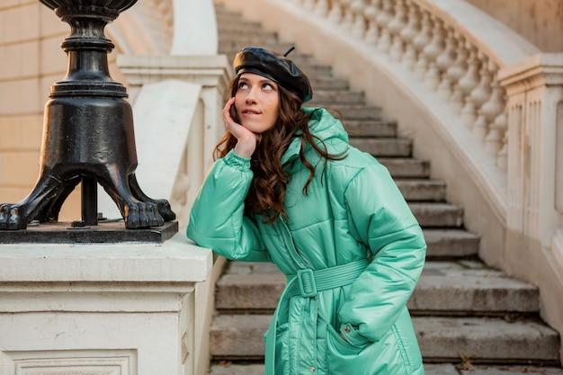 Romantische lächelnde stilvolle frau, die im winterherbstmode-trend blauen puffermantel und hutmütze in der alten schönen straßentreppe aufwirft