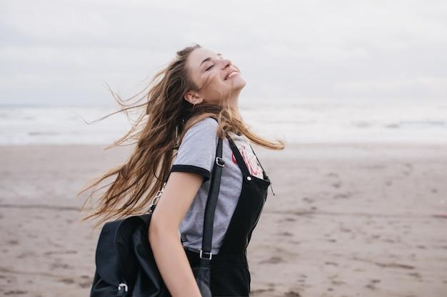 Romantische langhaarige frau mit schwarzem rucksack, die guten tag am sandstrand genießt. außenaufnahme des kaukasischen reizenden mädchens springend.