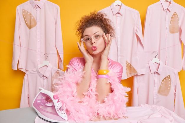 Romantische, lockige junge frau hält die lippen gefaltet, trägt eine transparente brille und bügelt zu hause, gekleidet in morgenmantel-posen gegen die gelbe wand. hausarbeit und hauswirtschaftskonzept