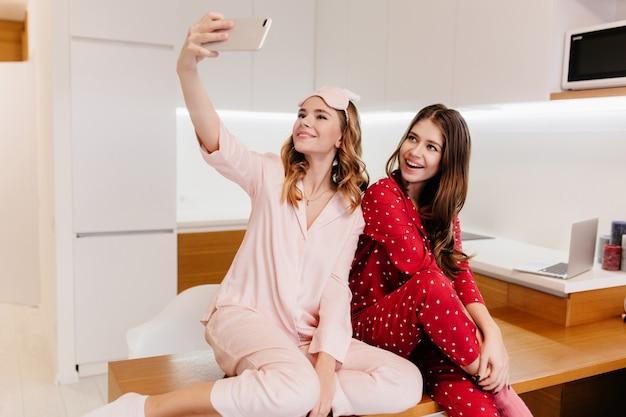 Romantische mädchen, die zusammen auf holztisch sitzen und sich selbst fotografieren. innenaufnahme von reizenden damen im pyjama, die selfie in der küche machen.