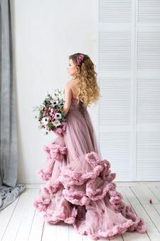 Romantische modefrau in einem rosa kleid und blumenstrauß.