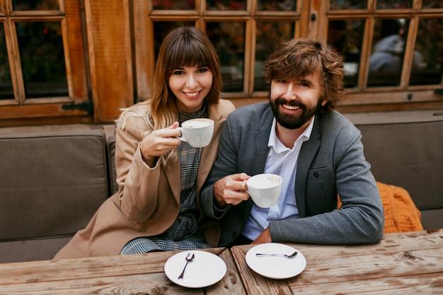 Romantische momente eines eleganten verliebten paares, das in einem café sitzt, kaffee trinkt, sich unterhält und die zeit miteinander genießt.