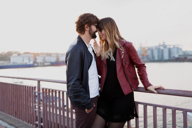 Romantische momente eines stilvollen paares, das sich verliebt, ein gespräch führt und die zeit miteinander genießt. hübscher mann mit seiner frau, die auf der brücke geht.