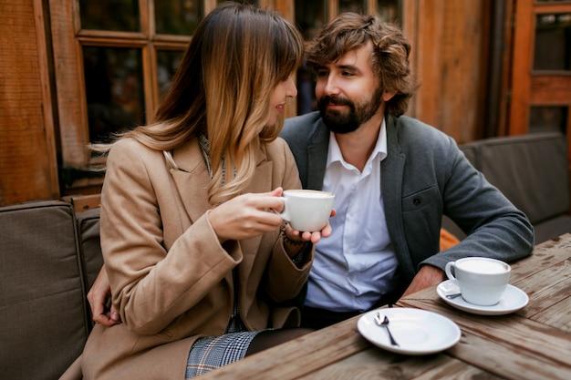 Romantische nachdenkliche frau mit langen welligen haaren, die ihren mann mit bart umarmen. elegantes paar, das im café mit heißem cappuccino sitzt.