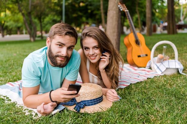 Romantische paare auf dem picknick unter verwendung app am handy, am mann und an der frau, die im urlaub smartphone verwendet