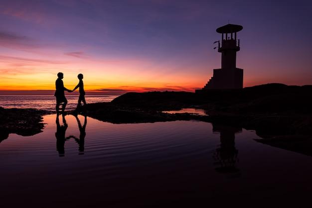 Romantische paare des schattenbildes mit leuchtturm zur sonnenuntergangzeit
