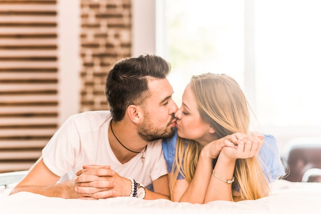 Romantische paare, die auf bett küssen