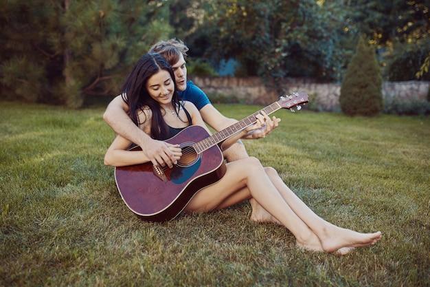 Romantische paare, die auf dem gras im garten sitzen