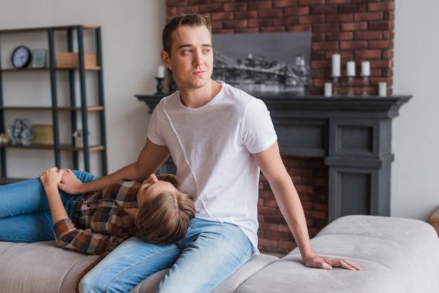 Romantische paare, die auf sofa sitzen und liegen
