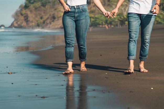 Romantische paare, die hand halten und auf strand gehen