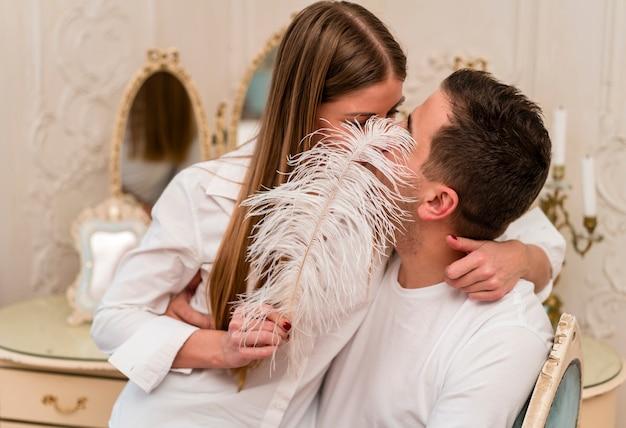 Romantische paare, die münder mit feder küssen und bedecken