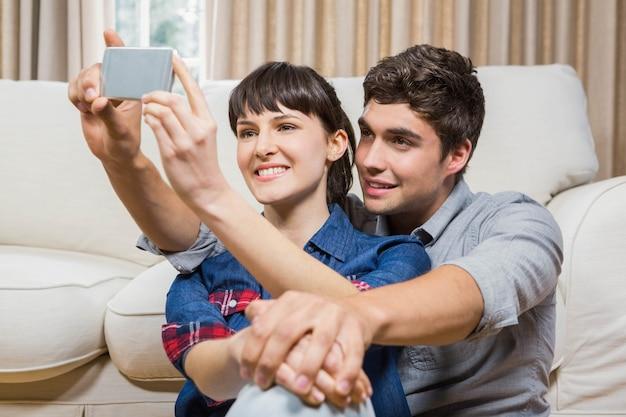 Romantische paare, die selfie in ihrem wohnzimmer nehmen