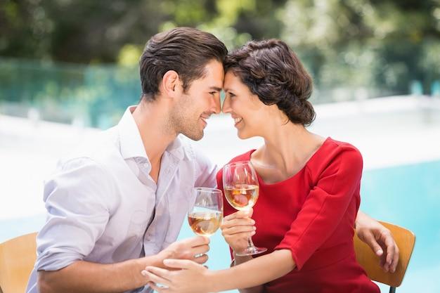 Romantische paare, die weißwein halten