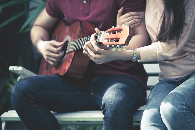Romantische paare, die zusammen gitarre zum liebes- und valentinstagkonzept spielen.