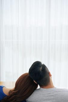Romantische paare, die zusammen zu hause auf couch vor fenster und rührenden köpfen sitzen