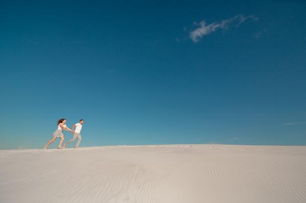 Romantische paare in der liebe, die auf weißem sand in der wüste läuft