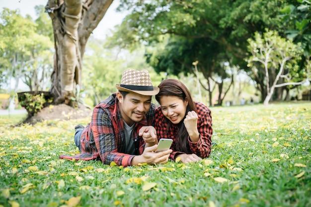 Romantische paare von den jungen leuten, die auf gras im park liegen.
