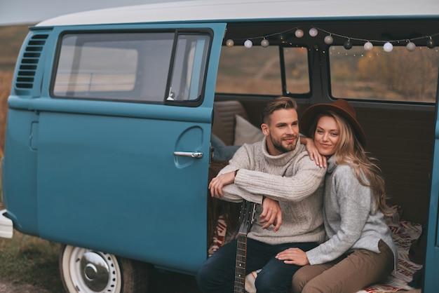Romantische reise. schönes junges paar, das lächelt und weg schaut, während es im blauen retro-art-minivan sitzt