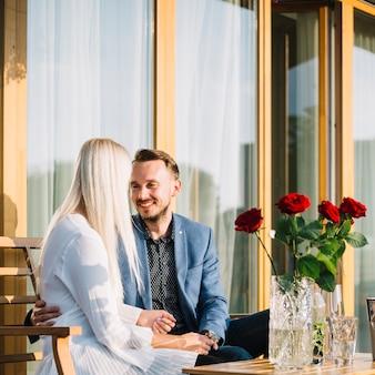 Romantische reizende junge paare, die im restaurant sitzen