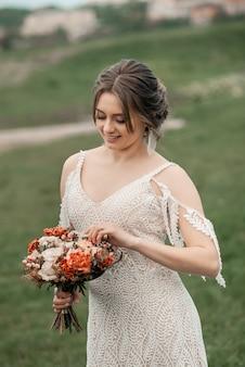 Romantische schöne braut im luxuskleid, das mit blumen nahe dem ort der hochzeitszeremonie aufwirft