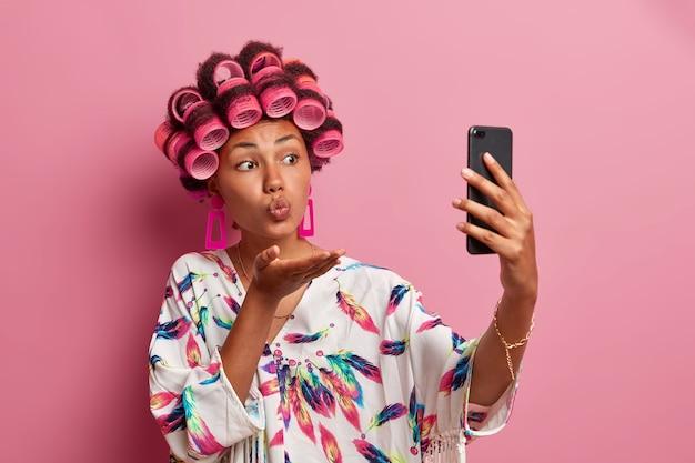 Romantische schöne frau mit lockenwicklern auf dem kopf nach dem duschen, nimmt selfie-porträt über handy, bläst mwah, trägt lässige hauskleidung, genießt videoanruf mit freund, hat natürliche schönheit