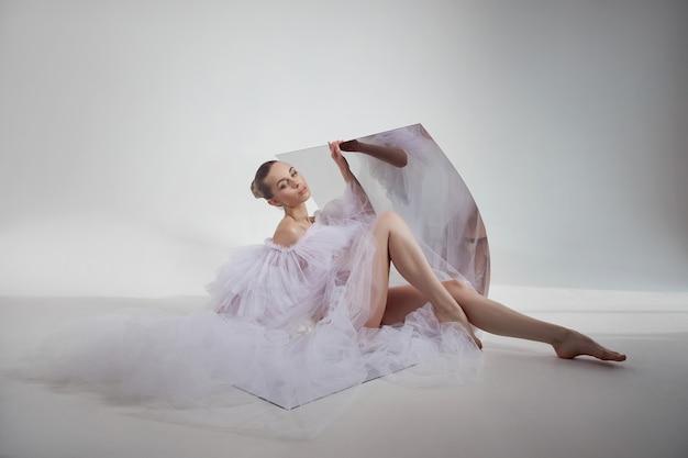 Romantische schönheitsfrau in einem hellen transparenten kleid wird in einem flexiblen spiegel reflektiert, der auf dem boden sitzt. perfekter körper und lange beine