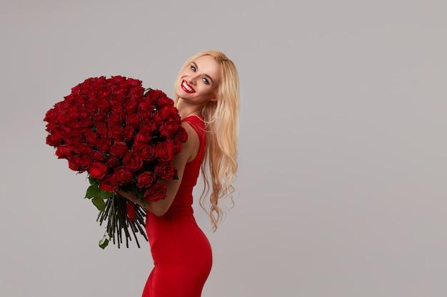 Romantische schönheitsfrau mit blumenstrauß der roten rosenblumen. rote lippen. valentinstag