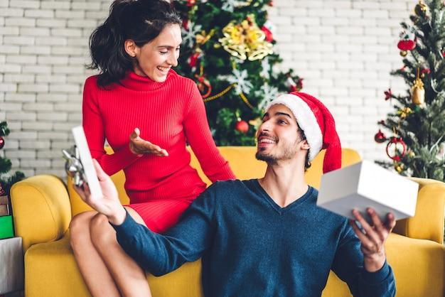 Romantische süße paare in sankt-hüten, die spaß haben, weihnachtsbaum zu verzieren und beim feiern des neujahrsabends und genießen, zeit zusammen zu verbringen zu lächeln mann, der der frau geschenkboxüberraschung gibt