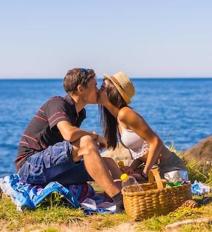 Romantische szene eines kaukasischen paares, das sich beim picknick in den bergen am meer küsst und die hitze genießt